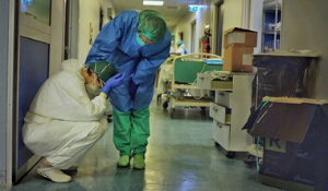 A grieving doctor is consoled by their colleague
